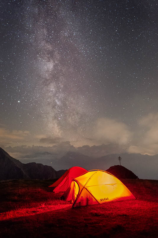 Milchstraße über beleuchteten Zelten in den Alpen auf dem Gipfel eines Berges