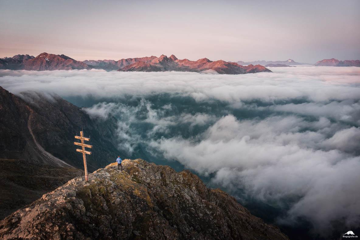 Drohnenfoto zum Sonnenaufgang am Gipfelkreuz in den Alpen