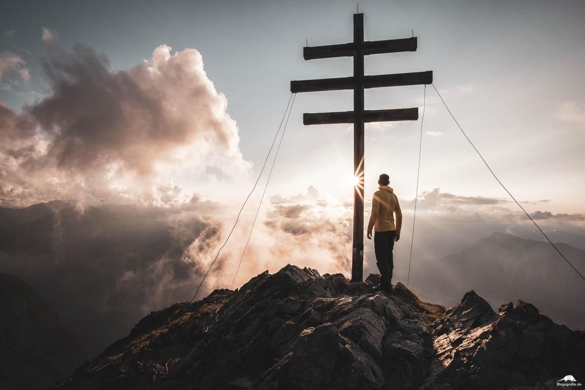 Wanderer am Gipfelkreuz zum Sonnenuntergang