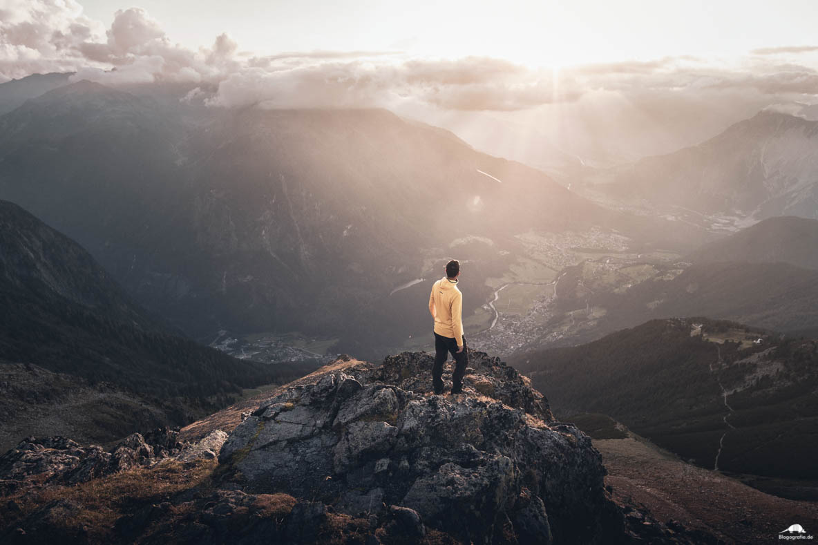 Wanderer in den Alpen mit Blick ins Tal zum Sonnenuntergang
