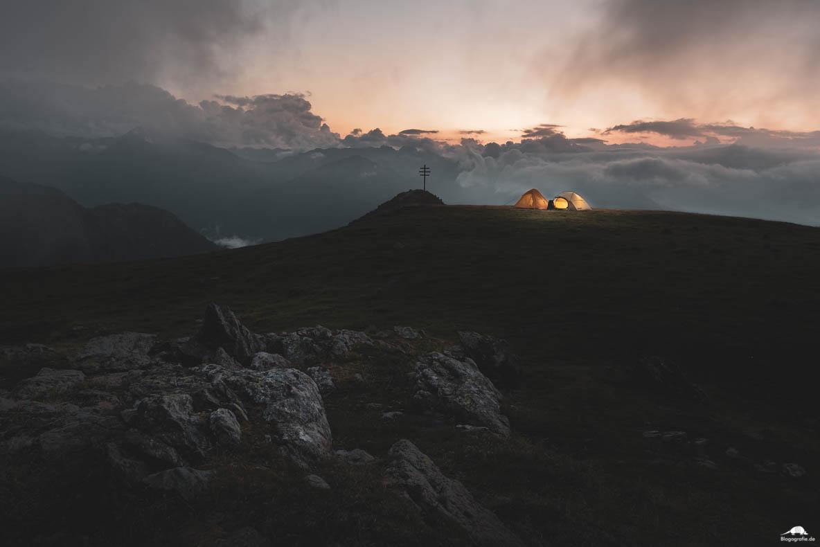 Zelte in der Dämmerung am Gipfelkreuz in den Alpen