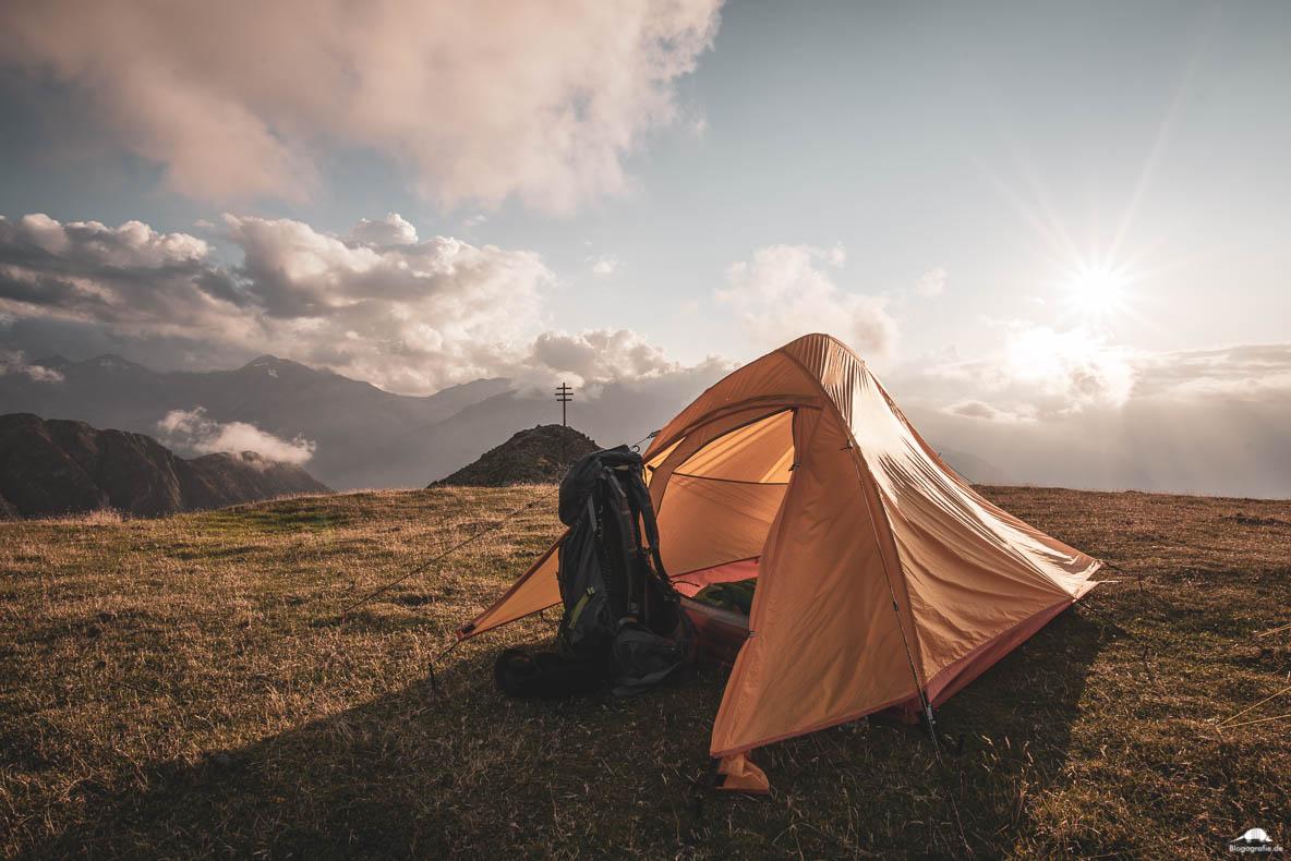 Zelt auf einer Wiese, kurz vorm Gipfelkreuz in den Alpen