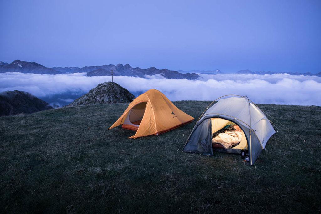 Zwei zelten auf einer Wiese über den Wolken in den Alpen am Gipfelkreuz auf 2600m Höhe