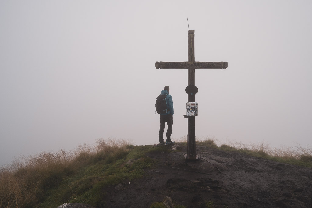 Wanderer am Gipfelkreuz der Gasselhöhe im Nebel