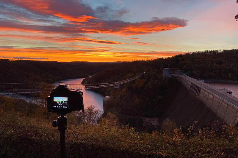 Rappbodetalsperre zum Sonnenaufgang mit Kamera und Stativ als Making-Of-Foto
