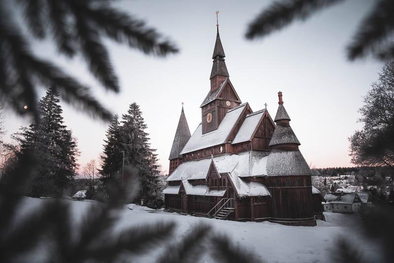 Stabkirche Hahnenklee zum Sonnenaufgang im Schnee mit Tannenzweigen