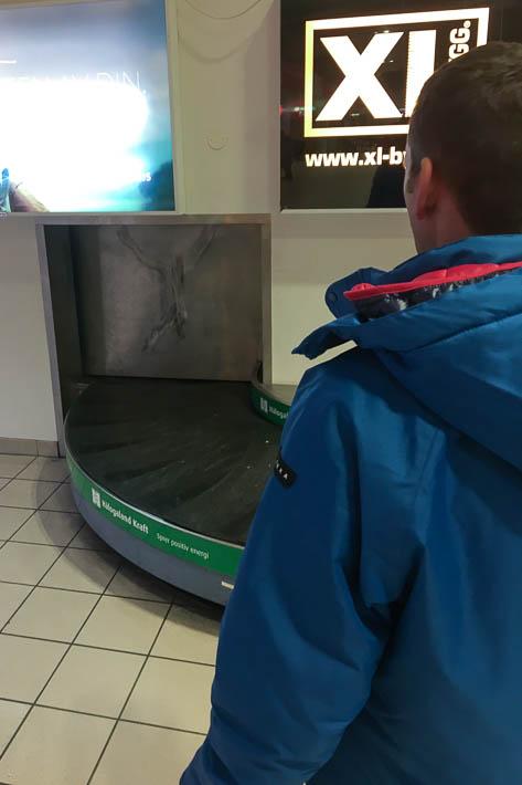 Thomas am leeren Gepäckband am Flughafen in Harstad Narvik auf den Lofoten