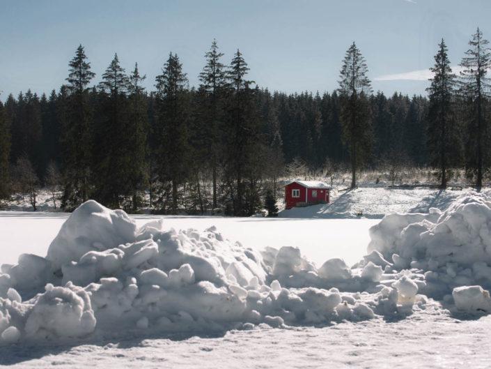 Rote Holzhütte am Ziegenberger Badeteich im Schnee